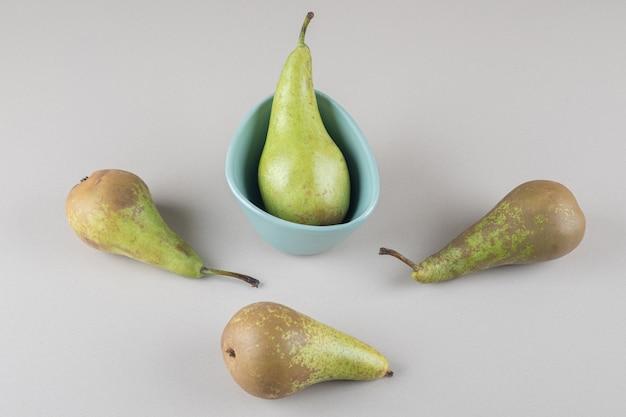 Sappige peren in en naast een kommetje op marmer