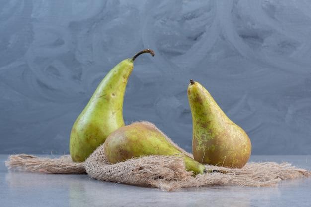Sappige peren op een stuk doek op marmeren achtergrond.
