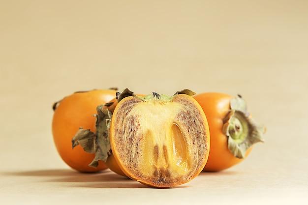 Sappige persimmon op een beige bedachtergrond.