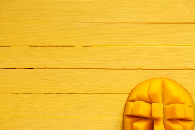 Sappige plak van mango op een gele achtergrond