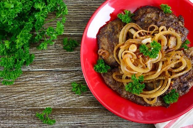 Sappige plakjes gebakken lever en uien op een rode plaat. bovenaanzicht.