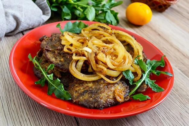 Sappige plakjes gebakken lever en uien op een rode plaat.