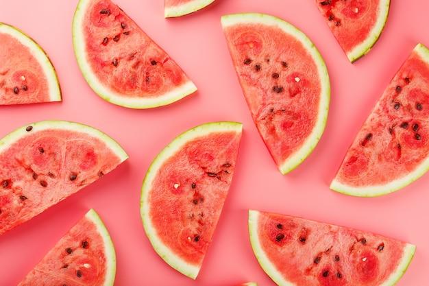 Sappige plakjes rode watermeloen op een fel roze. zomerse kleuren. patronen bovenaanzicht als een of substraat