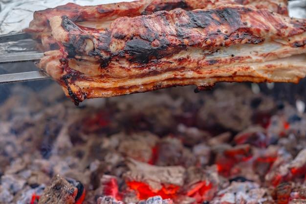 Sappige plakjes varkensvlees worden aan spiesen geregen en gegrild op houtskoolgrill