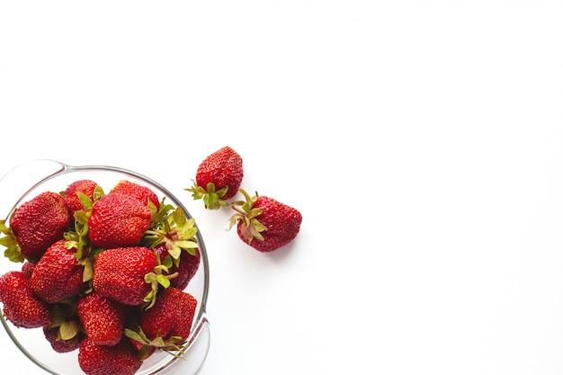 Sappige rijpe aardbeien in een kom die op een witte achtergrond met ruimte voor tekst wordt geïsoleerd