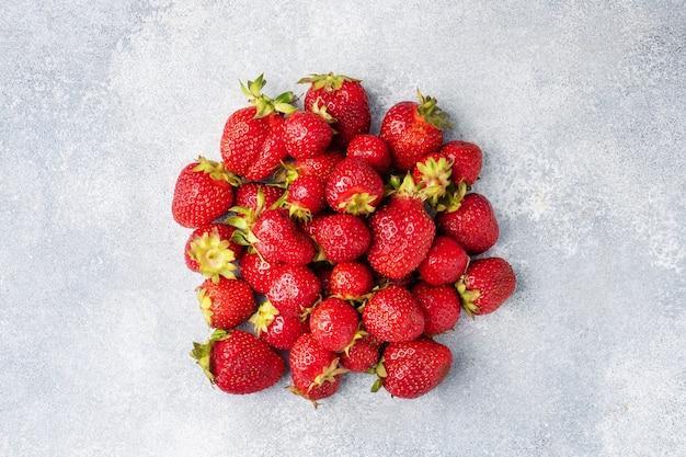 Sappige rijpe aardbeien op een betonnen ondergrond. zoet gezond dessert, vitamineoogst. ruimte kopiëren.