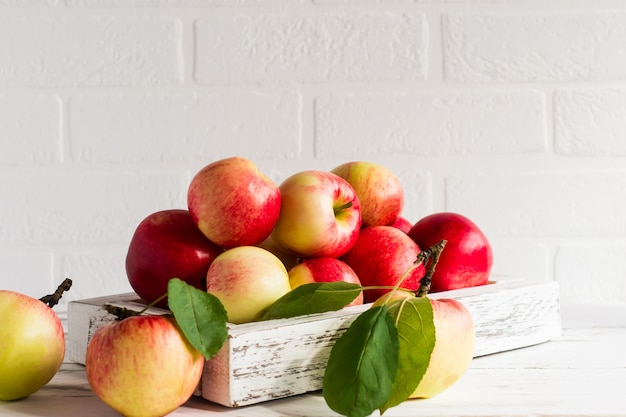 Sappige rijpe appels in een houten kist op een witte tafel tegenover de bakstenen muur.