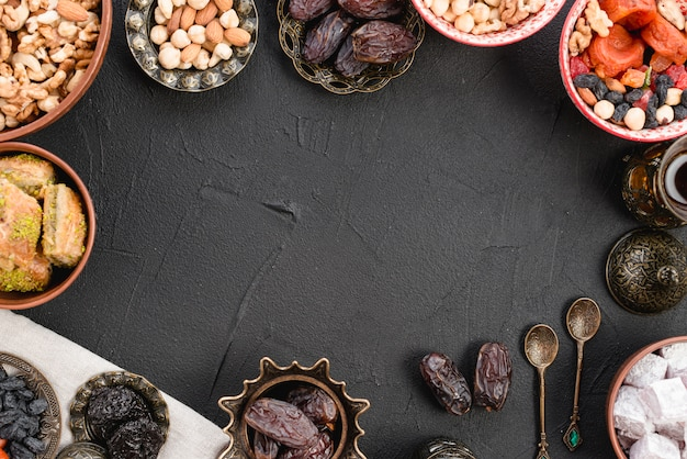 Sappige rijpe dadels; noten; lukum en baklava op zwarte concrete achtergrond