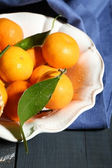 Sappige rijpe mandarijnen met bladeren op houten tafel