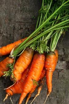 Sappige rijpe wortelen met groene toppen op een oude houten tafel. vitaminen en gezonde voeding uit de natuur. detailopname. verticaal.