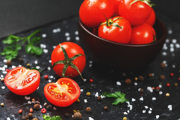 Sappige rode kerstomaten met kruiden, grof zout en greens. zoete en rijpe tomaten voor salades en als ingrediënten voor het koken