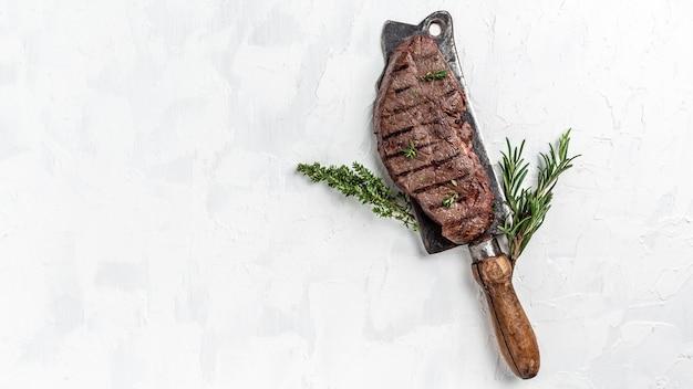 Sappige runderbiefstuk van medium rood marmer rundvlees geserveerd op oude vleesslager op lichte achtergrond, lang spandoekformaat, bovenaanzicht.