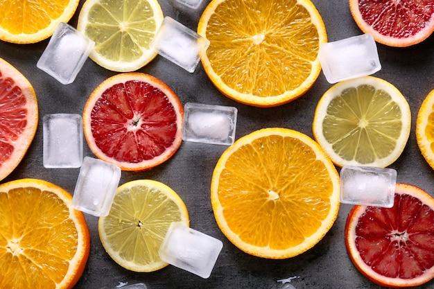 Sappige samenstelling van citrusvruchten en ijsblokjes op grunge achtergrond