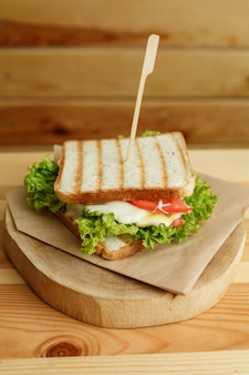 Sappige sandwich met spek, verse groenten, groene salade en donkere lijnen na grill op houten plaat