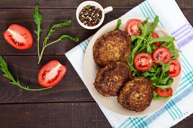 Sappige schnitzels op een plaat met een salade van tomaten en rucola op een donkere houten.
