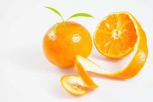 Sappige sinaasappel in een gepelde die sinaasappel op witte achtergrond wordt geïsoleerd