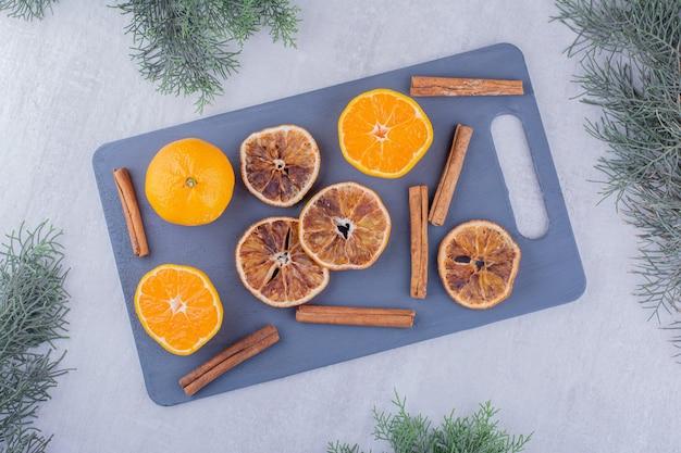 Sappige sinaasappelen, gedroogde plakjes en kaneelstokjes op een snijplank op witte achtergrond.