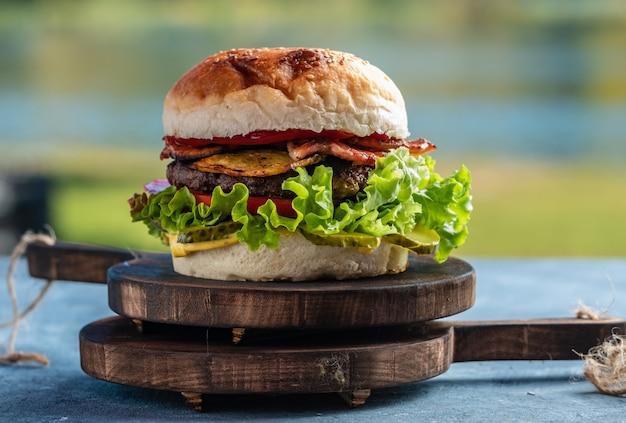 Sappige smakelijke cheeseburger met rundvlees, sla, augurken, tomaat en uienringen op een houten tafel. klassiek straatvoedsel - gegrilde hamburger