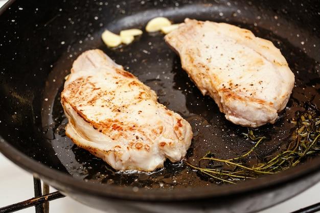 Sappige varkenssteaks in de pan, top van kookvoedsel