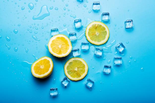 Sappige vers geel gesneden citroen en ijsblokjes op een blauw