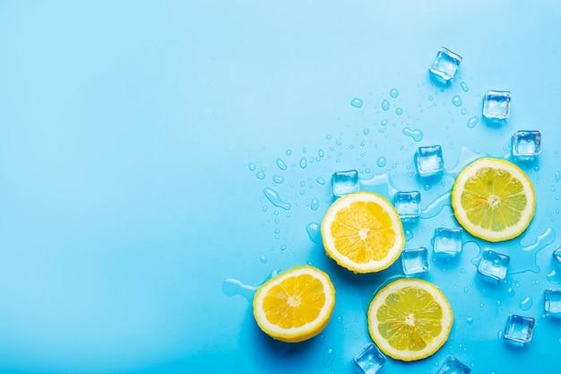 Sappige verse gele citroenplakken en ijsblokjes op een blauw