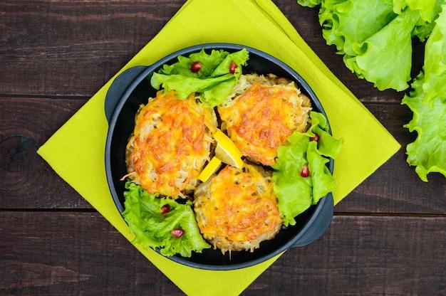 Sappige vleeskotelet, gebakken met geraspte aardappelen en kaas op een gietijzeren koekenpan op een donkere houten tafel. bovenaanzicht