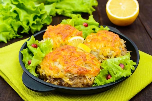 Sappige vleeskotelet, gebakken met geraspte aardappelen en kaas op een gietijzeren koekenpan op een donkere houten tafel. detailopname