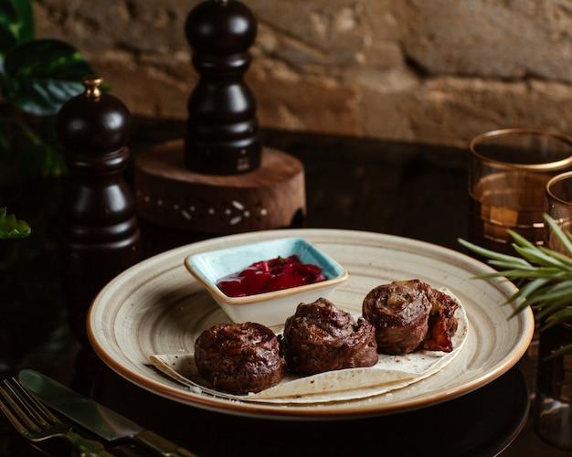 Sappige vleesstukken op pitabroodje met saus
