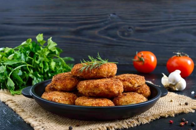 Sappige zelfgemaakte koteletten (rundvlees, varkensvlees, kip) op een zwarte achtergrond.