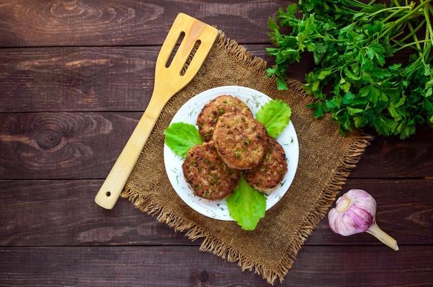 Sappige zelfgemaakte schnitzels (rundvlees, varkensvlees, kip) op een houten achtergrond. voor een hamburger. het bovenaanzicht.