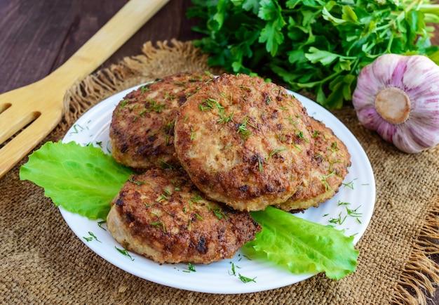Sappige zelfgemaakte schnitzels (rundvlees, varkensvlees, kip) op een houten achtergrond. voor een hamburger.