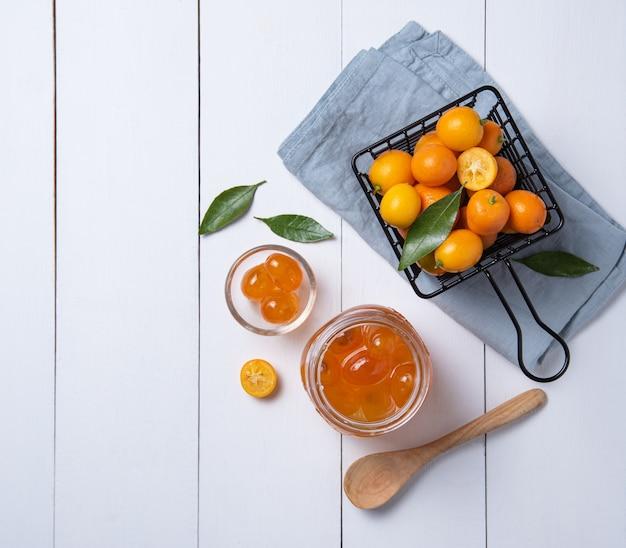 Sappige zoete kumquats liggen in een doos en een pot met jam op een witte houten tafel