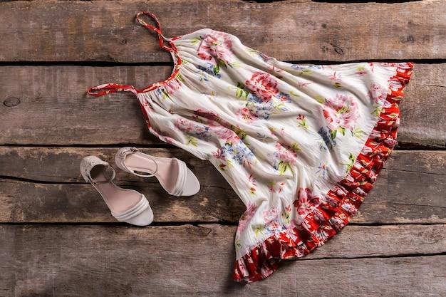 Sarafan met beige hakschoenen. sarafan op oude bruine vloer. retro zomerkleding uitverkoop. vrouwen droegen dit jaren geleden.