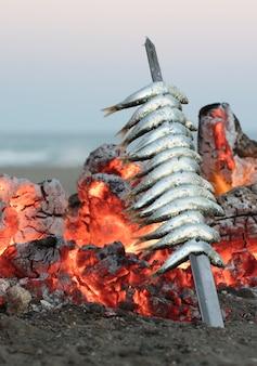 Sardinedikte met vuur bij zonsondergang typisch mediterraan eten uit de stad malaga