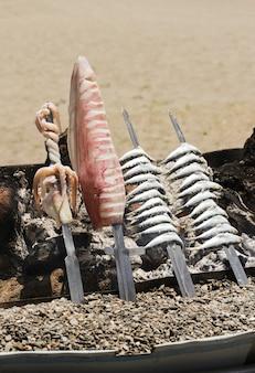 Sardines en inktvis spies zandstrand achtergrond