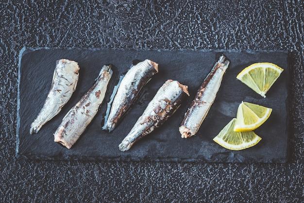 Sardines op de zwarte stenen bord