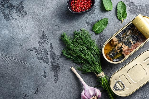 Sardinops in olie in conserven van ingeblikt voedsel, gesloten en open blik met kruiden en knoflook ocer grijze achtergrond overhead gewasruimte voor tekst.
