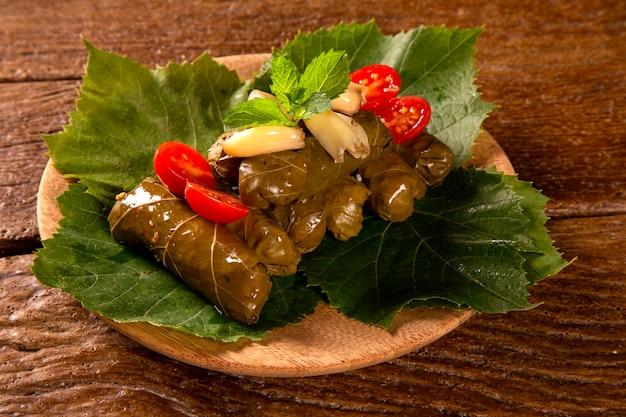 Sarma - rijst en munt die in wijnstokbladeren op houten achtergrond wordt verpakt.