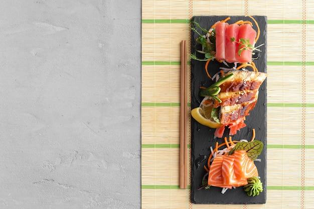Sashimi sushi van zalm, paling en tonijn geserveerd op plaat close-up