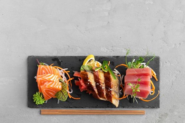 Sashimi sushi van zalm, paling en tonijn geserveerd op plaat