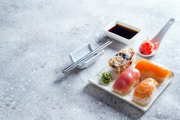 Sashimi, uramaki en nighiri met rijst, zalm of tonijn, garnalen in steen