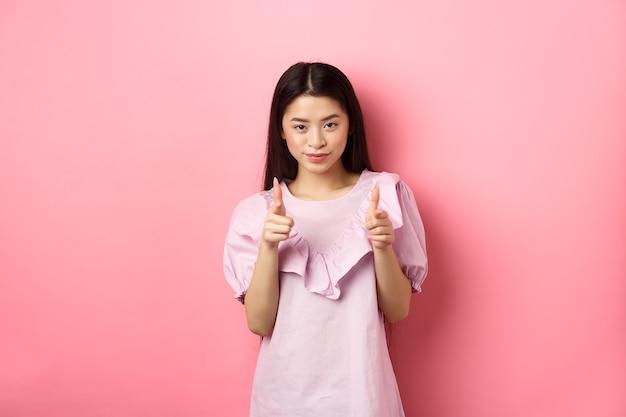 Sassy aziatische vrouw wijzend op de camera, lacht en nodigt u uit, wenkt of prijs persoon, staande op roze achtergrond.