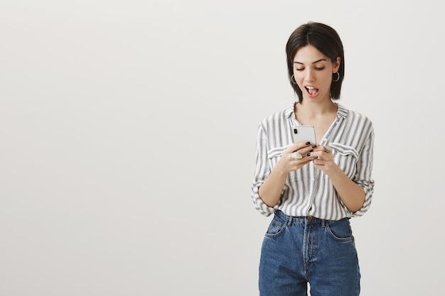 Sassy brunette meisje messaging, mobiele telefoon bezet kijken