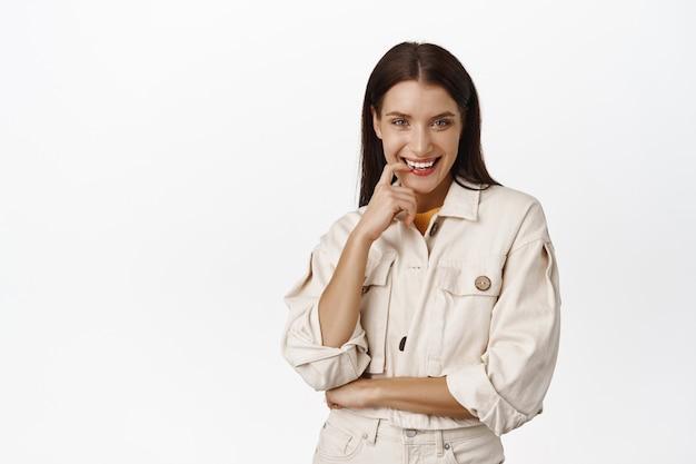 Sassy brunette vrouw, flirterig lachend, vinger bijtend en sluw lachend, heeft iets in gedachten, denkend en koket kijkend, staande op wit.