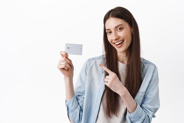 Sassy cool meisje, wijzend op creditcard en glimlachen, bank aanbevelen, in vrijetijdskleding tegen witte muur staan