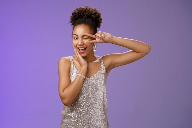 Sassy elegante zelfverzekerde afro-amerikaanse vrouw in stijlvolle zilveren jurk touch wang toon vrede overwinning gebaar voel geluk zelfverzekerd draag luxe jurk bijwonen rijke partij, blauwe achtergrond.