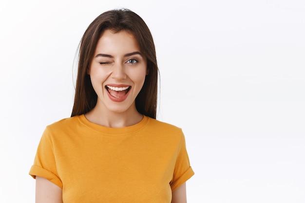 Sassy en brutale knappe brunette vrouw knipogen aantrekkelijk meisje staande in de buurt van bar, zelfverzekerd en zelfverzekerd glimlachen als haar nummer vragen, staande witte achtergrond vrolijk
