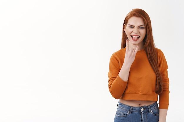Sassy en gedurfde knappe roodharige studente promoten iets spannends, activiteit of evenement. aantrekkelijke gembervrouw die rock-n-roll-gebaar en stoktong toont, staande witte muur