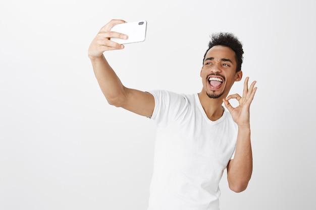 Sassy glimlachende afro-amerikaanse mannelijke student selfie met mobiele telefoon te nemen, ok gebaar tonen