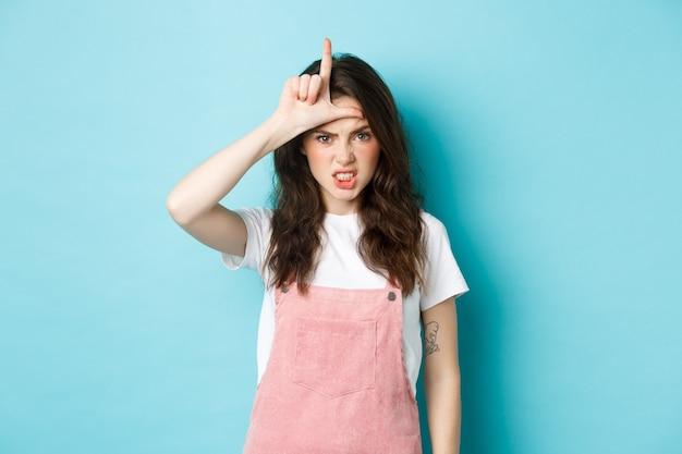 Sassy jonge vrouw veracht haar rivaal, toont verliezersgebaar op het voorhoofd, maakt letter l met de hand en staart met ontzetting naar de camera, staande tegen een blauwe achtergrond